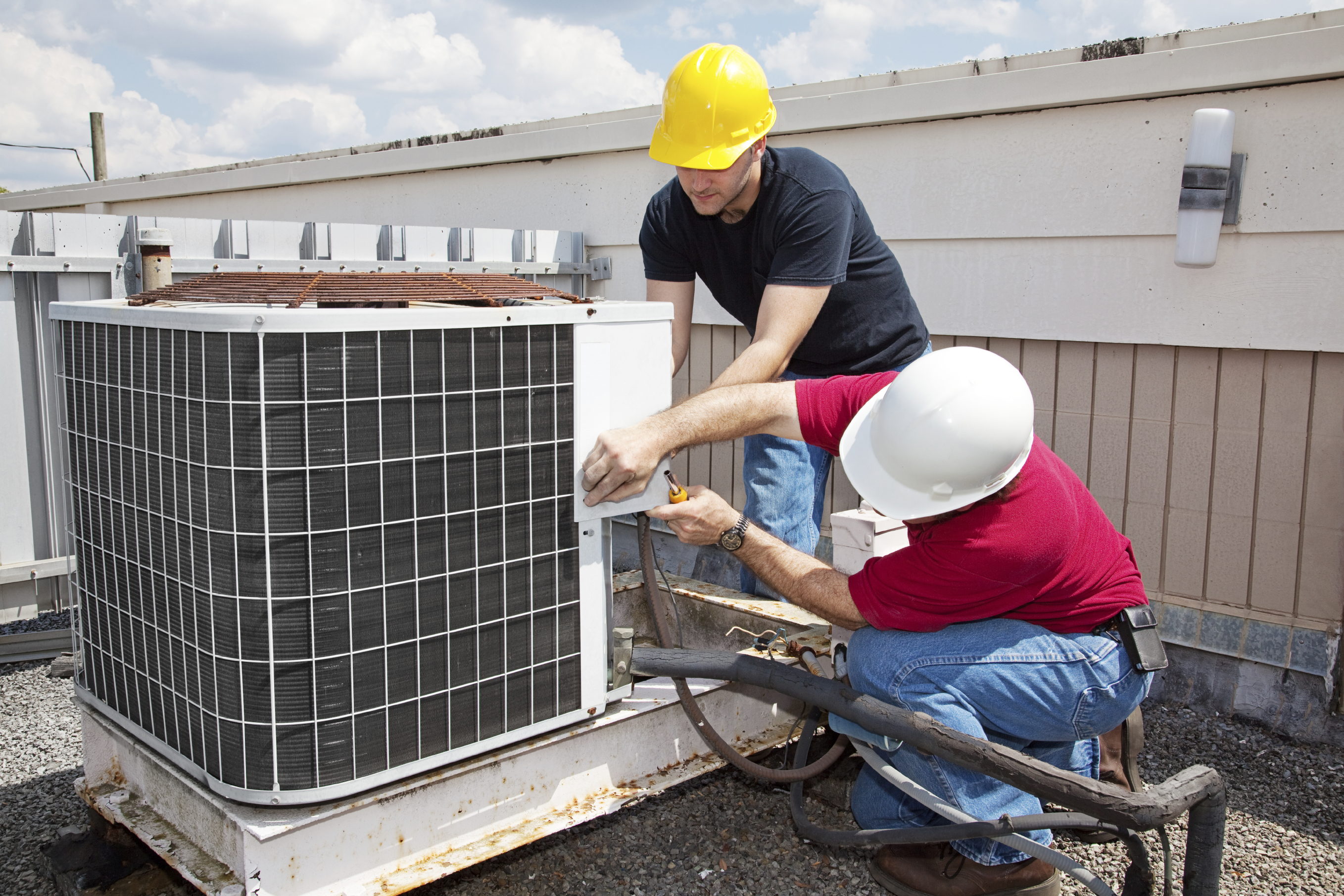 Two workers on the roof of a building working on the air conditioning unit.